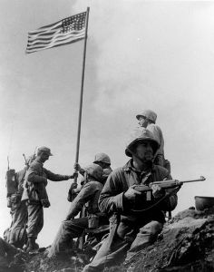 First Iwo Jima Flag being raised, a small flag carried ashore by the 2d Battalion, 28th Marines, being planted on Mount Suribachi February 23, 1945. The more famous picture, with a larger flag, was staged later. That image is copyrighted. This one is in the public domain because it came from the US Marine Corps. Both picutres can be found on Wikipedia. [Click the image to go there.]