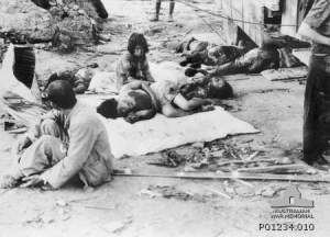 Hiroshima street scence after the atomic bomb. Civilian casualties waiting for medical help.