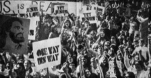 "A Jesus People gathering: a crowd of young people carrying signs that say ""one way"" and ""try Jesus"""