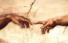 Closeup of fingers touching from the Creation of Adam painting in the Sistine Chapel.