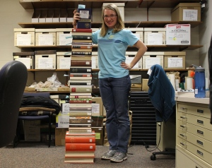 Student standing beside a stack of books as tall as she is.