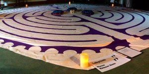 A cloth with a labyrinth outline on the ground, lit by candles along the edges
