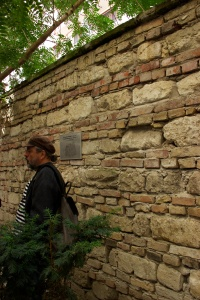 man standing next to a stone wall