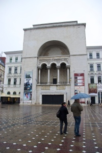 Front of opera house with two people standing outside holding an umbrella