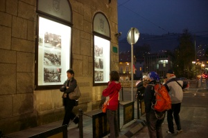street corner at night with people looking at exhibit in windows