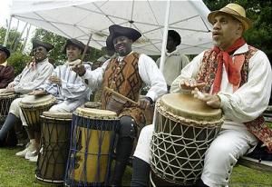 African american men wearing colonial tricorn hats and playing west African drums.