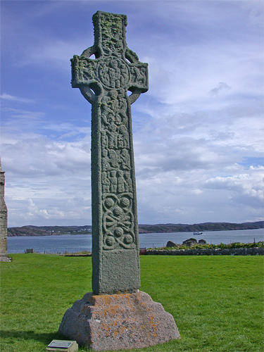 celtic cross against a cloudy sky with coast in the distance