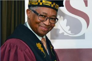 smiling Russel Botman wearing university robes
