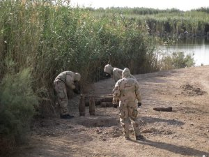 Soldiers in chemical protection gear, including Sgt. Eric J. Duling and Specialist Andrew T. Goldman, examining suspected chemical munitions at a site near Camp Taji, Iraq, on Aug. 16, 2008. Source: The New York Times