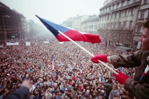 Crowd of people, with student waving Czechoslovakian flag in the foreground
