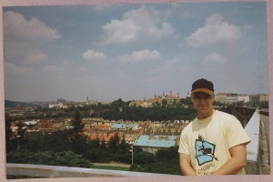Prof. Berglund in a t-shirt and baseball cap posing in front of the Prague skyline on a summer day