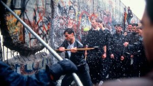 A man hammering at the Berlin Wall soaked by water.