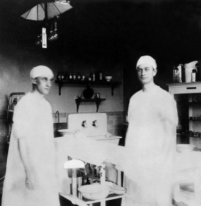 two young men in surgical scrubs in an operating room.
