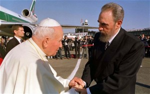 Pope John Paul II shakes hands with Fidel Castro at an airport surrounded by crowds of onlookers