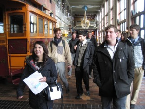 Group of students in the museum atrium next to a train car.