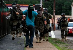 Heavily armed police in riot gear approach an African-American man with his hands raised.