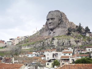 Colossal stone sculpture of Ataturk's face on the mountaintop above hillside houses.