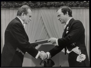 Milosz accepts his award and shakes the presenter's hand.