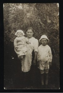 Black and white photo of two young boys with their nanny.