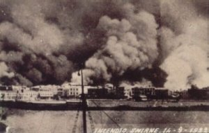 black and white photo of harbor with surrounding buildings thick with smoke