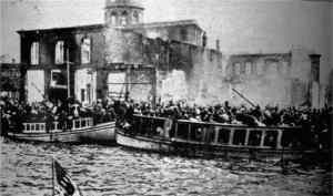 Black & white photo of crowded boats in front of burning buildings.