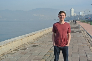 Post author Spencer Cone standing along the Izmir coast with modern buildings in the background.