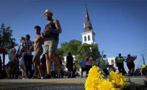 "People walk past a bunch of flowers left in memorial on the ground as they take part in a ""Black Lives Matter"" march past Emanuel AME Church on June 20, 2015"