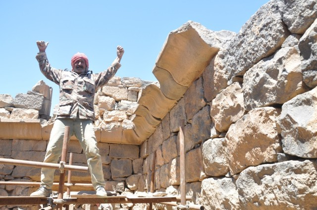 a worker stands triumphant in an archaeological dig site