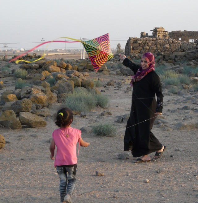 A girl and her mother fly a kite with ruins in the background.