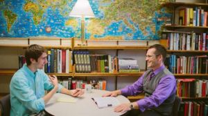 student and professor talk together over a table in the professor's office