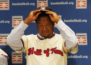 baseball player putting on his cap at a press conference