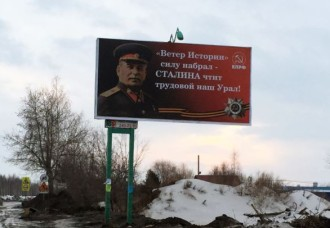 Billboard with uniformed Stalin, a slogan in Russian, and the hammer and sickle of the Communist Party.