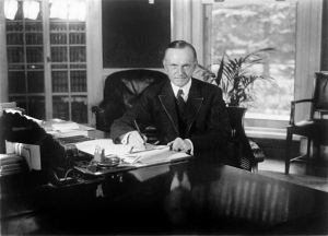 President Coolidge seated at his desk in the Oval Office.