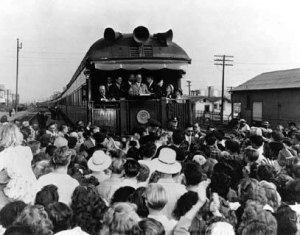 Harry Truman on back of train car speaking to crowd of people.