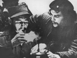 Fidel Castro (left) lights his cigar while Che Guevara looks on in the early days of their guerrilla campaign. (Image source: Hulton Archive/Getty Images, via NY Daily News.)