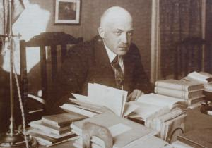 Black and white photo of balding man at a table surrounded by books.