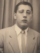 Sepia toned image of a young man wearing a suit coat and tie.