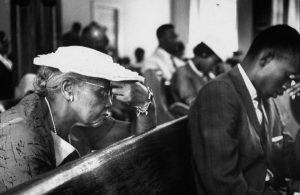 African-American woman praying in a church pew with other congregants in the background