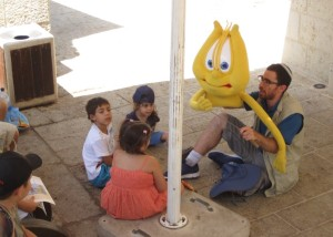 Man holding a large anthropomorphic harp puppet teaches a group of small children.