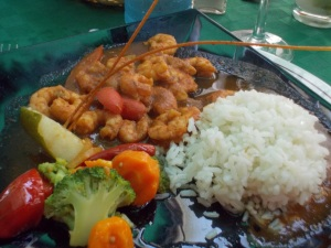 A plate showing a hearty meal of rice, vegetables, and shrimp.