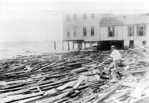 Black and white photo of flattened wood building on the coast.