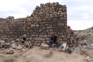 Three men break for tea next to an ancient stone wall ruin.