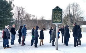 Group of students standing in the snow near a historic house museum sign.