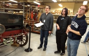 Students in a museum storage room near a historic car.