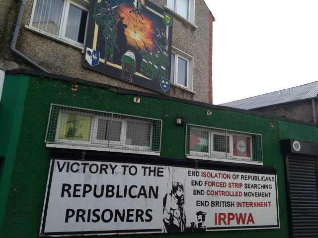 "Buildings painted with murals that say ""Join the IRA"" and ""Victory to the Republican Prisoners: End Isolation of Republicans, End Forced Strip Searching, End Controlled Movement, End British Internment IRPWA"""