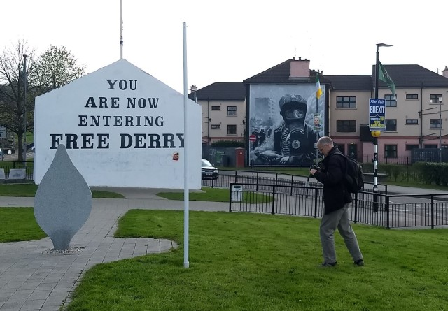 "Painted building with the text ""You are now entering Free Derry."" In the background, another building is painted with the image of a soldier in gas mask."