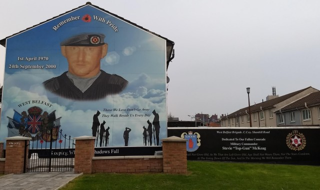 "Outdoor mural captioned ""Remember with Pride"" and ""Thoswe we Love Don't Go Away"" and ""Dedicated to our fallen comrade, military commander Stevie 'Top-Gun' McKeag.'"""