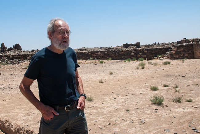 Bert de Vries stands outside the archaeological site at Umm el-Jimal Jordan. A sunny day in the desert with the foundation of ancient buildings in the background.